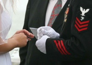 A Marine putting the wedding ring on his financee
