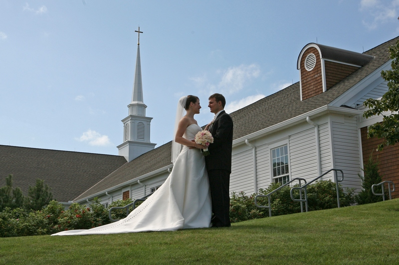 The wedding couple standing outside a Cape Cod church