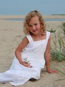 Little girl in a white dress, sitting on the beach, in a painted image