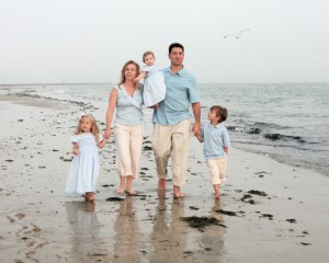 A family walking on a beach filled with seaweed